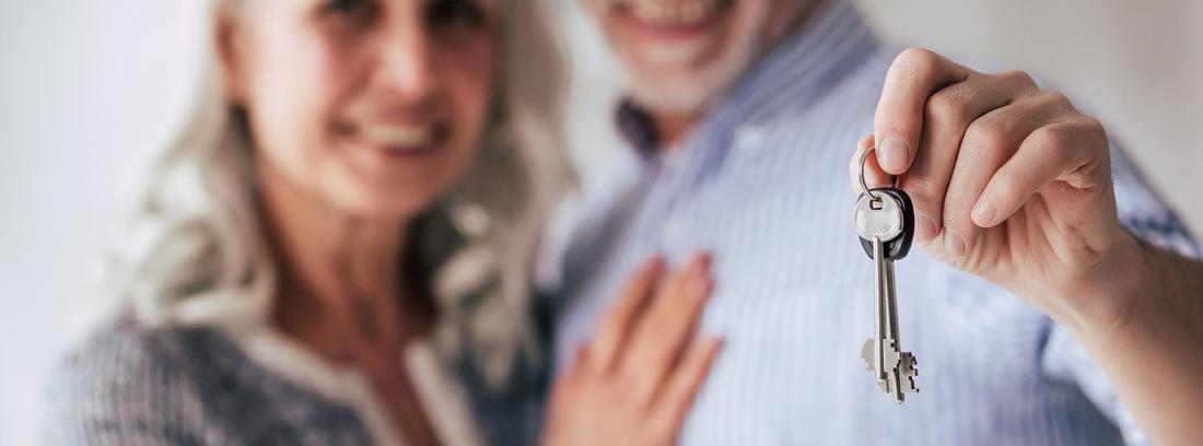 Hombre y mujer con pelo blanco sostienen unas llaves en la mano