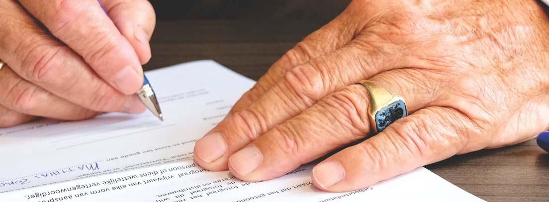 Manos con arrugas y anillo con bolígrafo sobre un papel