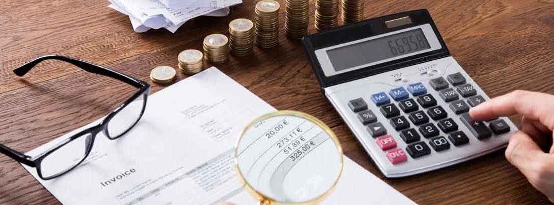 persona mirando con lupa una factura mientras suma en una calculadora
