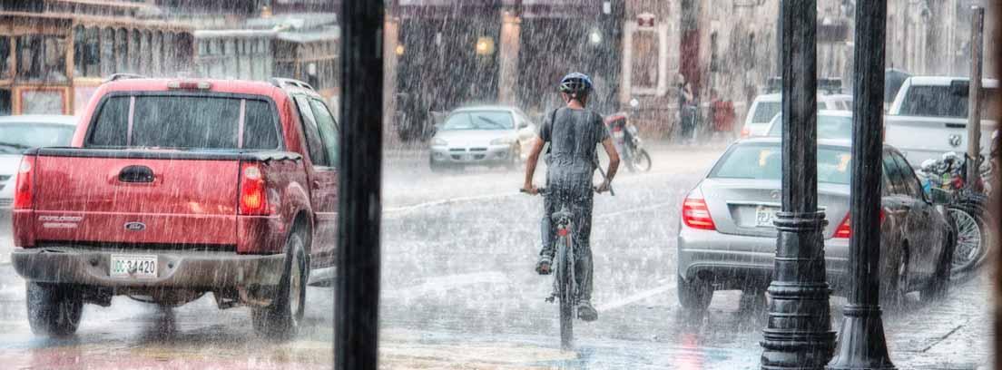 Calle de ciudad con coches y personas bajo una tupida lluvia