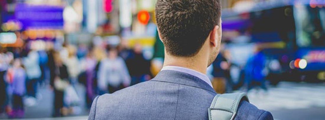 Hombre de espaldas en calle de una gran ciudad en busca de trabajo