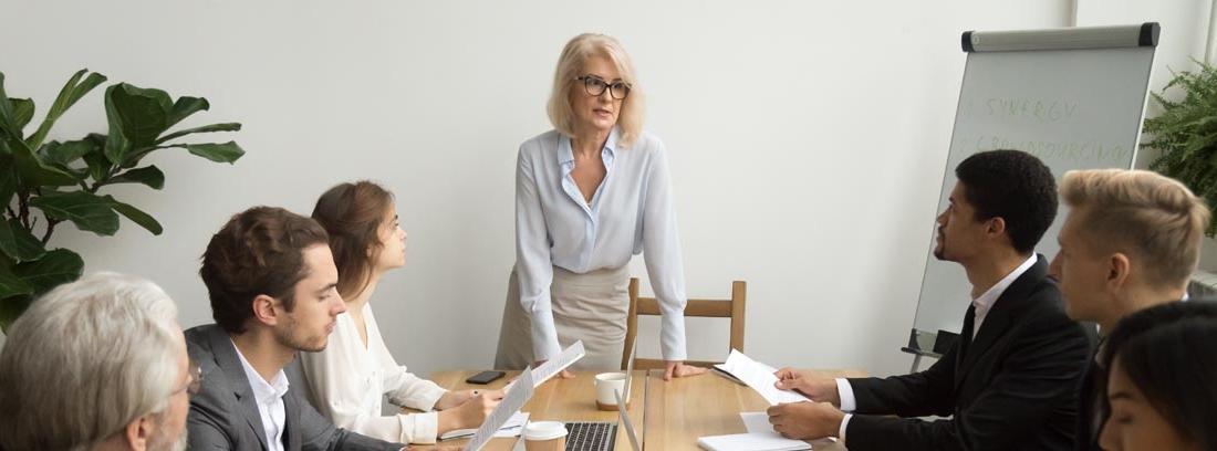Mujer de pie en una sala de reuniones hablando con un grupo de personas