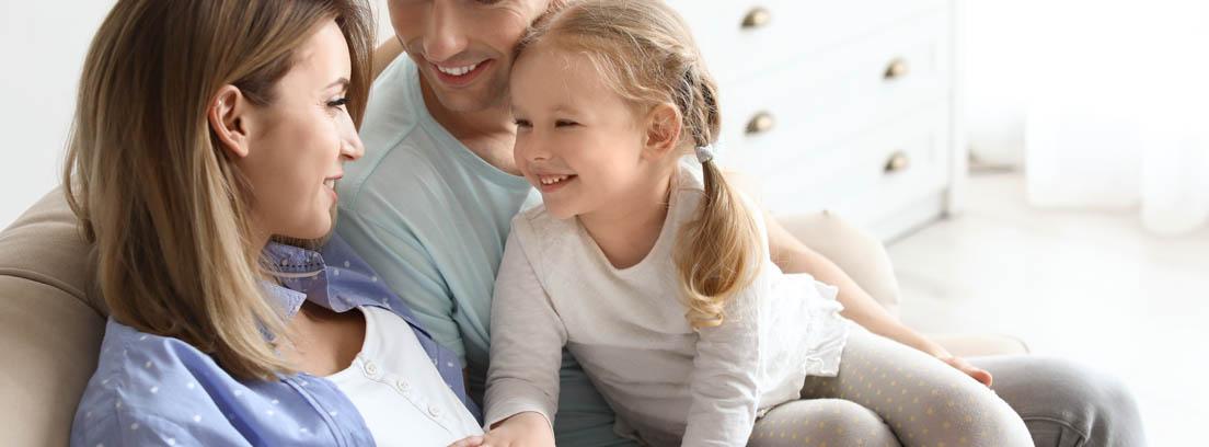 Mujer embarazada, hombre y niña sentados en un sofá