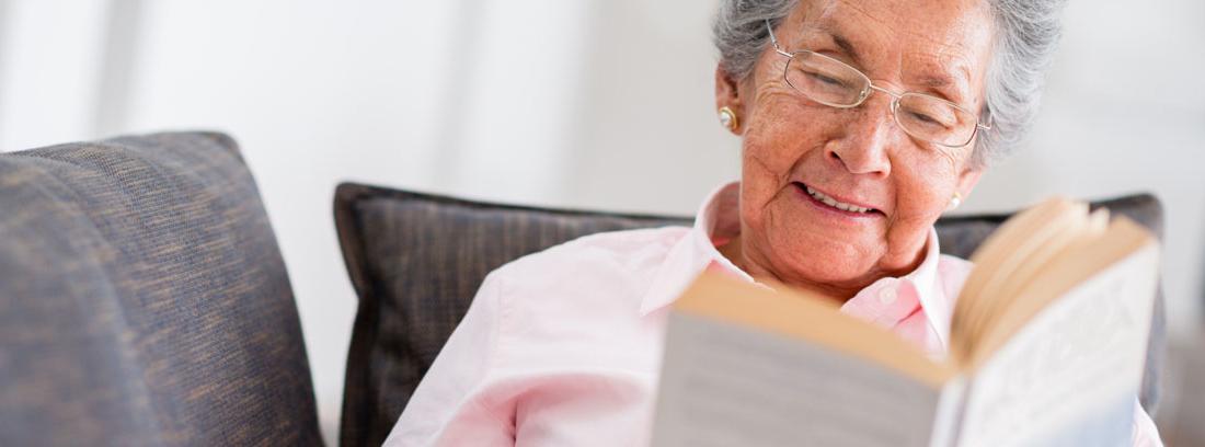 señora mayor leyendo un libro en un sofá
