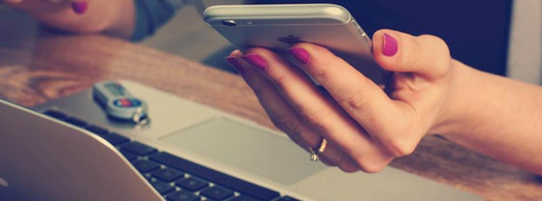 Mujer con móvil en la mano y delante de un ordenador portátil