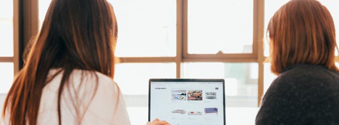 Dos personas delante de ordenador portátil