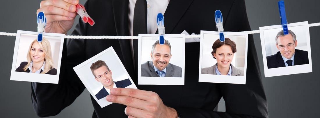 Hombre con traje cogiendo una foto de una cuerda de tender en la que hay más fotos de personas, como metáfora de contratar a alguien