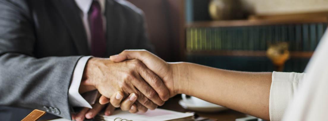 Dos personas estrechándose la manos sobre una mesa con papeles, como acuerdo ante un cambio de trabajo