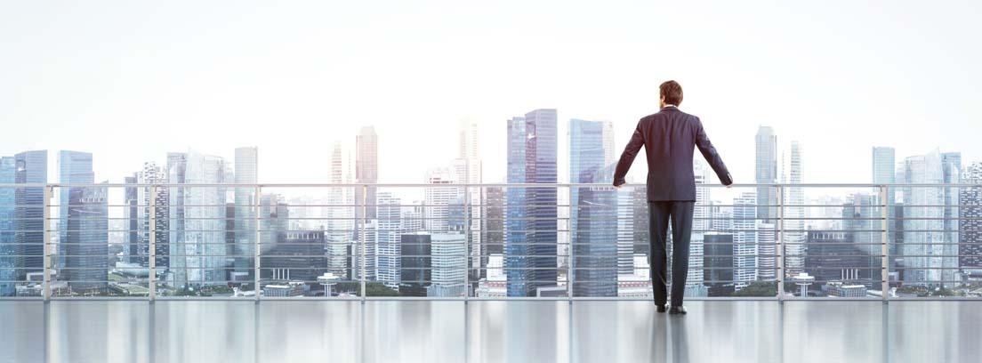 Hombre con traje de espaldas apoyado una barandilla observando los edificios de una ciudad