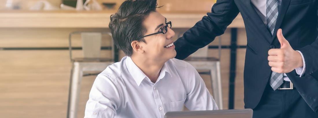 Hombre con pulgar en alto muestra su aprobación como jefe a un empleado