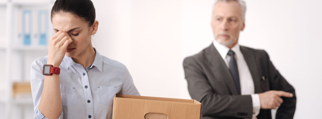 Hombre despidiendo a una mujer que porta una caja de cartón