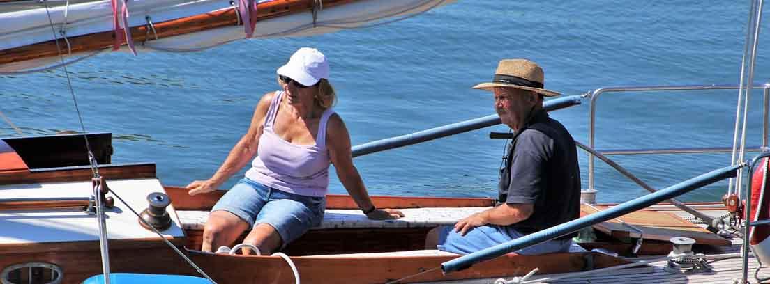 Hombre y mujer con gorros en la cubierta de un barco