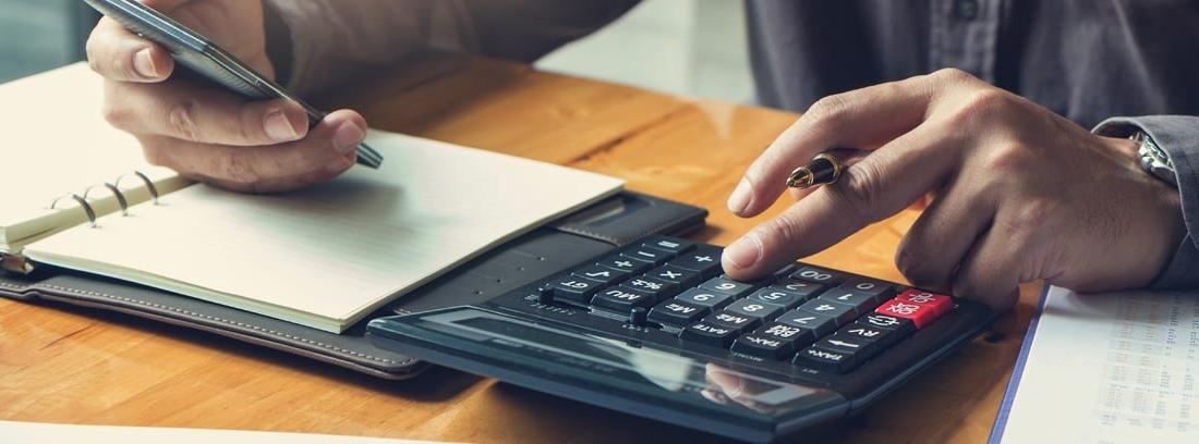 Persona con apuntes contables y calculadora descubriendo sus deducciones fiscales