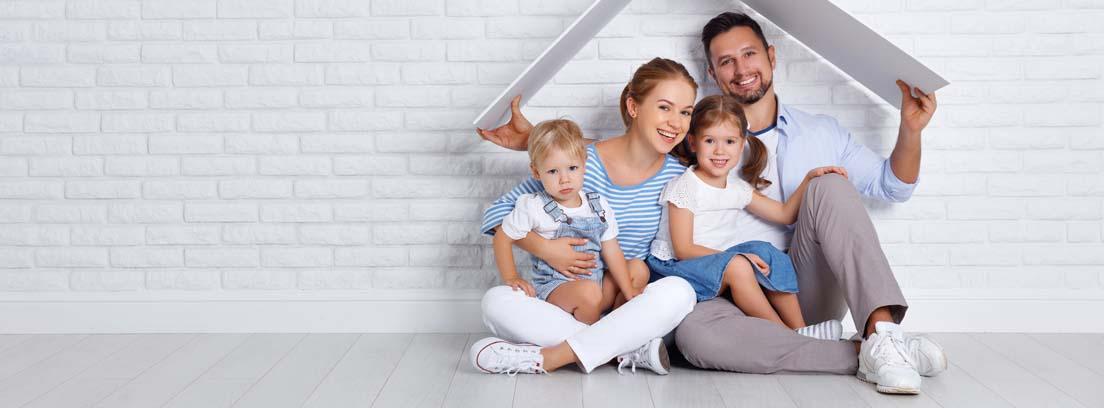 Familia sentada en el suelo sosteniendo un triángulo de cartón a modo de tejado