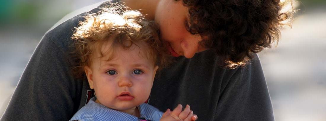 chico joven haciendo de canguro de un bebé