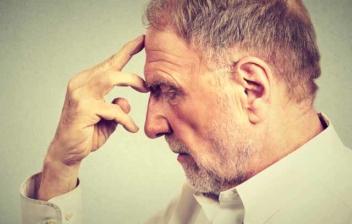 Hombre mayor con la mano en la frente y gesto pensativo
