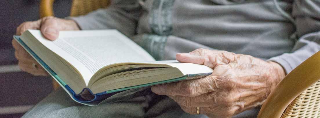 Manos de mujer mayor sujetando un libro abierto