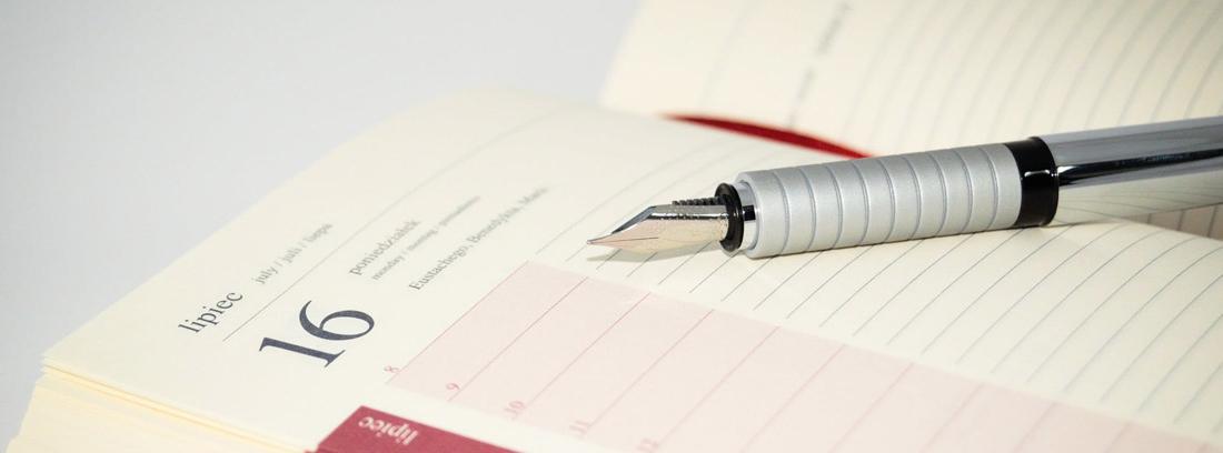 Agenda junto a pluma para elaborar calendario de ahorro