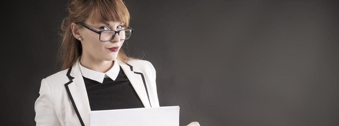 Mujer joven con gafas vestida elegante con un folio en sus manos