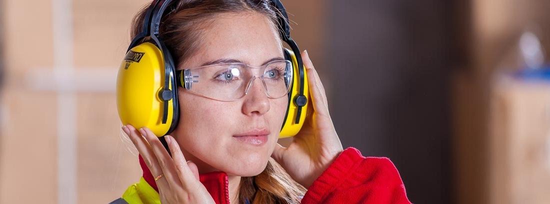 mujer con ropa de trabajo con cascos para proteger sus oídos