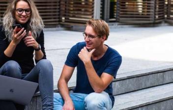 Grupo de tres jóvenes estudiantes con móvil y ordenador