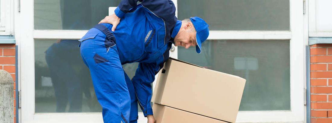 Repartidor llevándose una mano a la espalda mientras recoge unas cajas