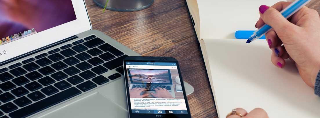 Persona con ordenador, papel y rotulador haciendo cuentas