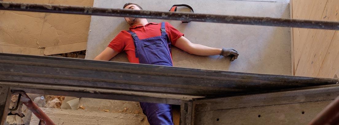 Trabajador en el suelo tras sufrir una caída