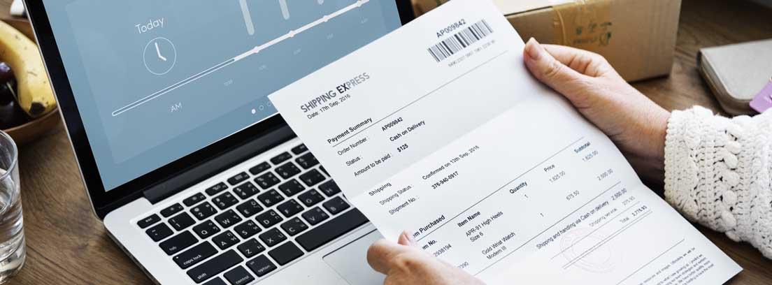 Hombre con una factura en la mano frente a un ordenador