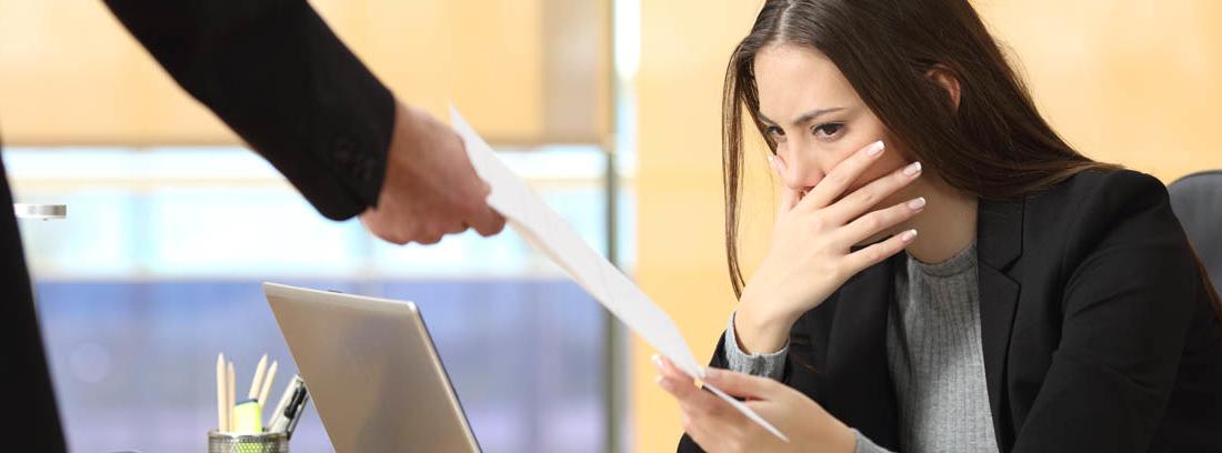 Mujer trabajadora sujeta un papel con gesto de preocupación