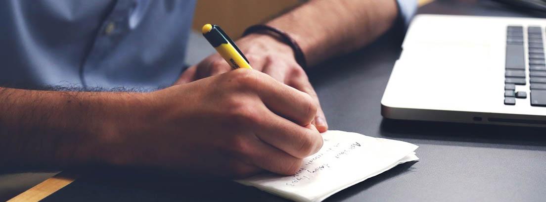 Manos con bolígrafo apuntando sobre papel