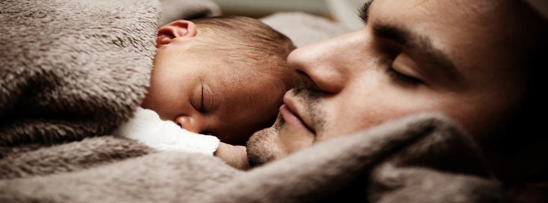 Un hombre y un bebé tapados con una manta durmiendo