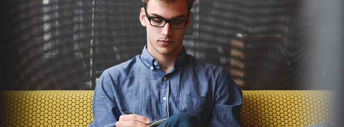 joven sentado en un sofá escribiendo en un papel