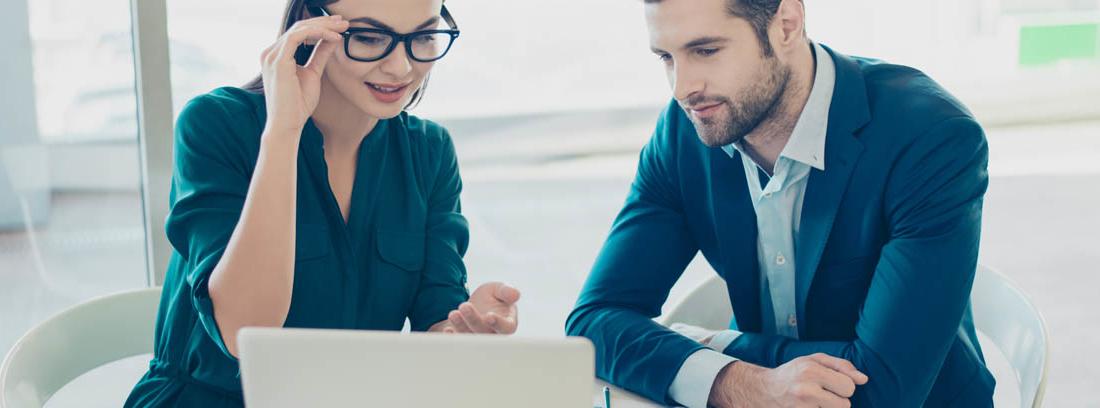 Hombre y mujer consultan un ordenador