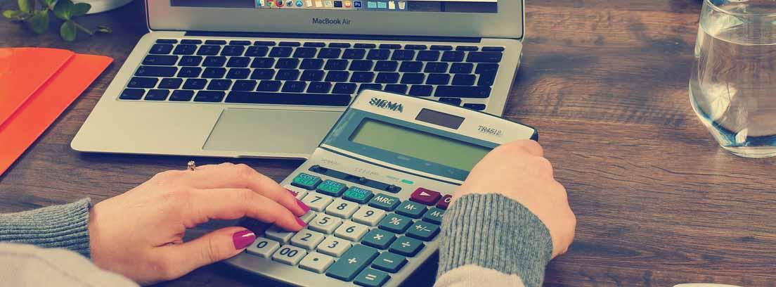 Mujer con una calculadora frente a un programa de contabilidad