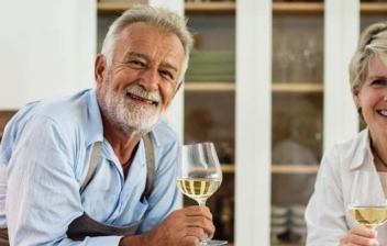 Hombre y mujer de pelo cano sonrientes en una cocina