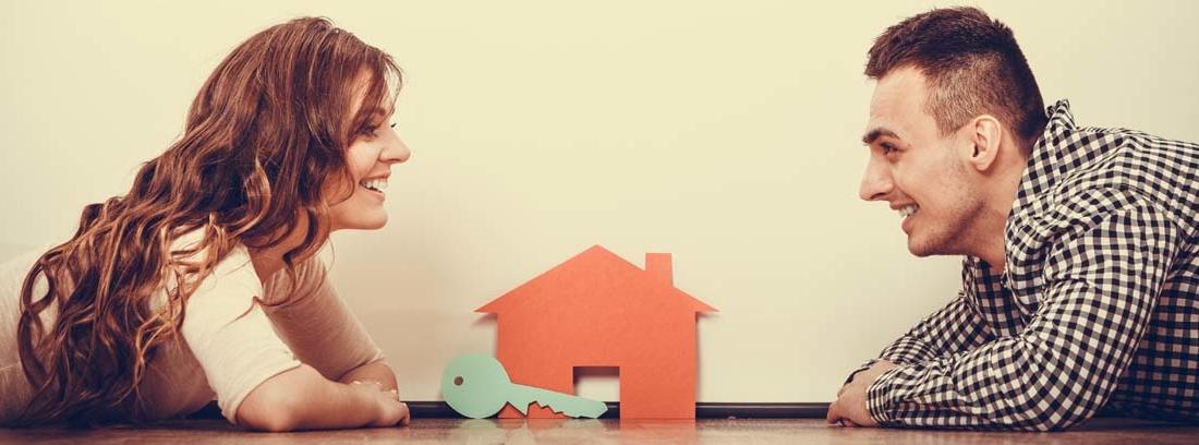 Hombre y mujer de frente tumbados en el suelo con una casa y una llave de cartón en el centro