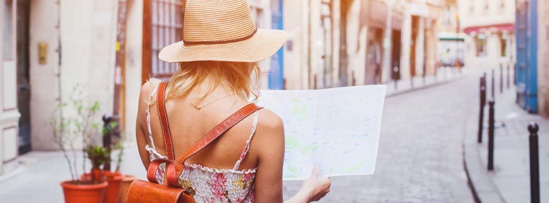 Mujer de espaldas con sombrero y mochila mirando un mapa en una calle con viviendas turísticas