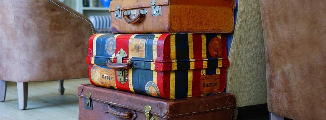 Tres maletas una encima de la otra entre de dos sillones marrones