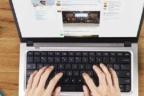 Vista cenital de unas manos sobre el teclado de un ordenador, una taza de café, unas gafas y un móvil con la pantalla de Twitter