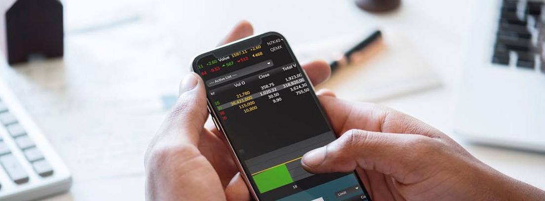 Manos sostienen móvil con pantalla con cifras