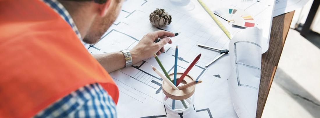 Trabajador con casco y chaleco delante de planos y papeles