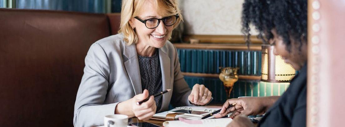 Dos mujeres sentadas con agendas y papeles sobre la mesa