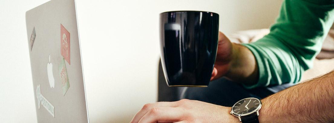 Hombre con una taza de café usando en un ordenador la oficina virtual de un banco sin oficinas
