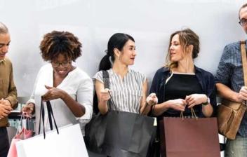 Grupo de hombres y mujeres con bolsas de compras