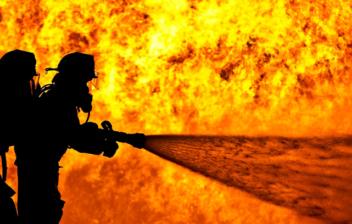 Silueta de dos bomberos delante de un fuego con una manguera, antes de llegar a la edad de jubilación de los bomberos