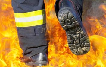 Piernas con uniforme de bombero pisando sobre unas llamas
