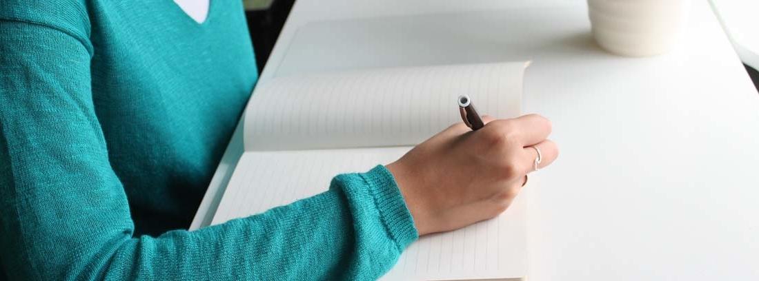 mujer escribiendo a mano una carta al Defensor del Pueblo