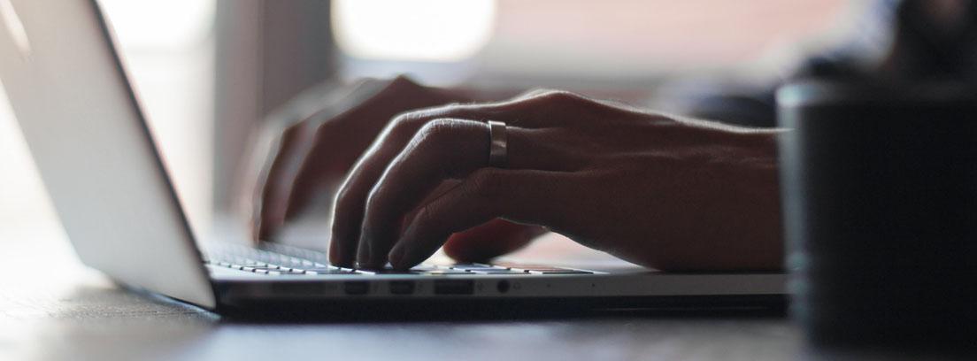 persona escribiendo en un ordenador una carta al Defensor del Pueblo