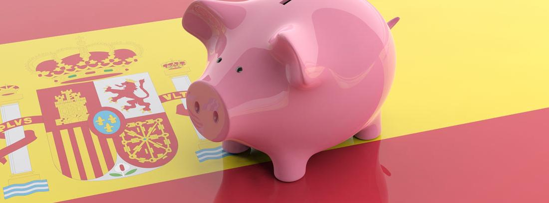 Hucha con forma de cerdo sobre la bandera de España